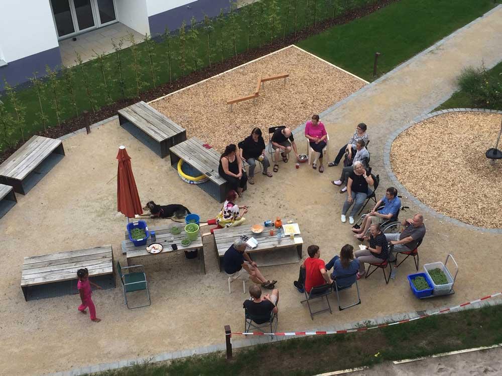 Foto zeigt den Innenhof des Wohnprojekts, in welchem sich mehrere Menschen versammelt haben
